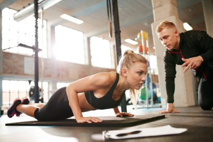 Indoor shot of young female exercising with personal trainer at gym. Fitness woman doing push ups with her personal trainer at health club.