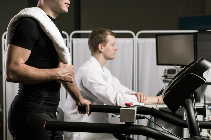 Close up of sportsman standing on treadmill and young medic in white uniform